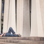 A man reclines in front of large columns; courtesy of gratisography.com