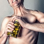 Man straining to open a pickle jar. Courtesy of gratisography.com