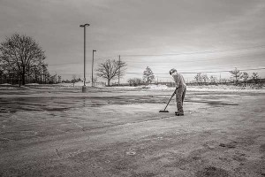 A solitary individual sweeping an empty parking lot. Courtesy of gratisography.com