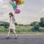 Solemn woman carrying balloons down the road; courtesy of Gratisography.com