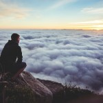 Man seeing the big picture over the clouds, courtesy of unsplash.com