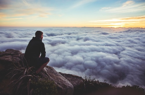 Man seeing the big picture over the clouds
